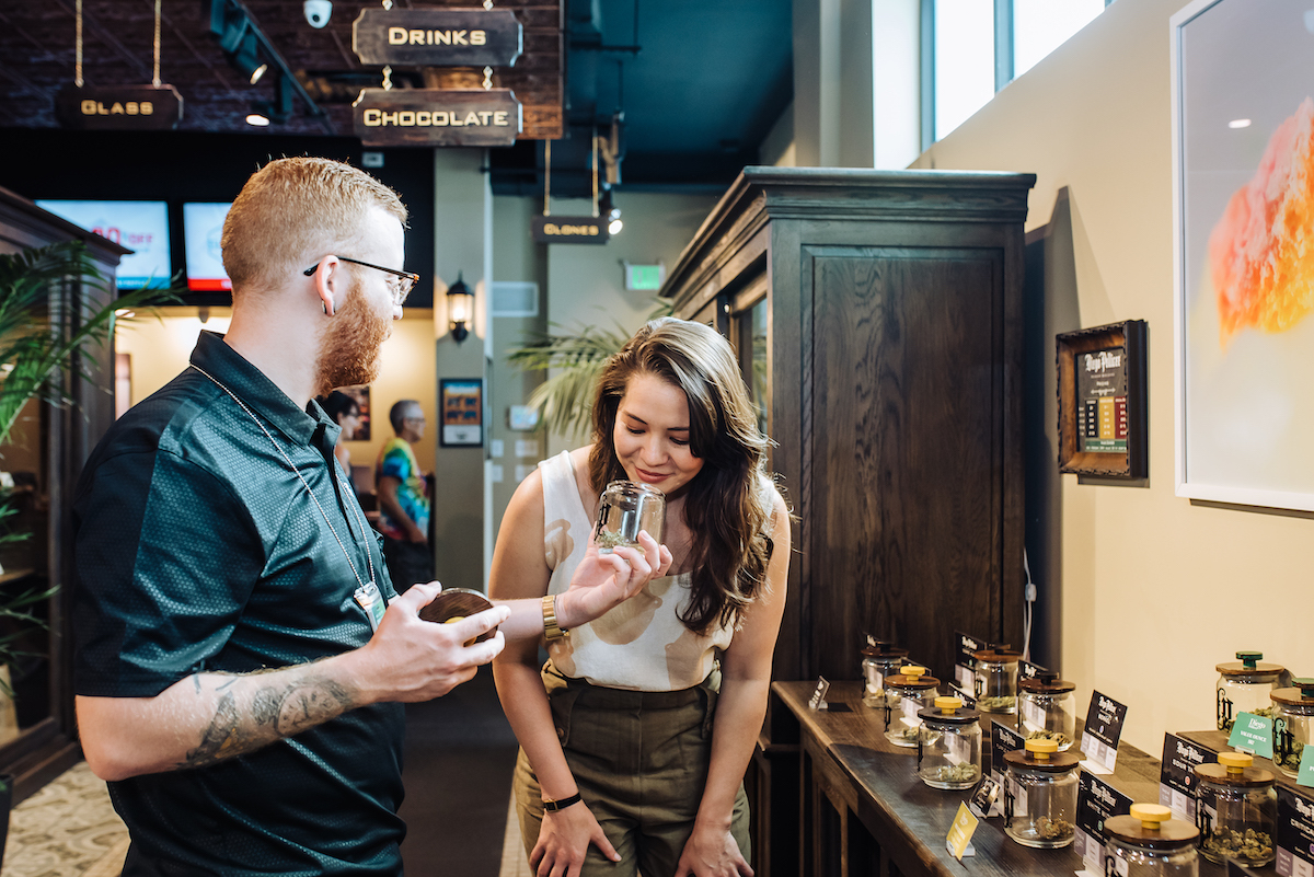 A customer smells cannabis flower at a dispensary
