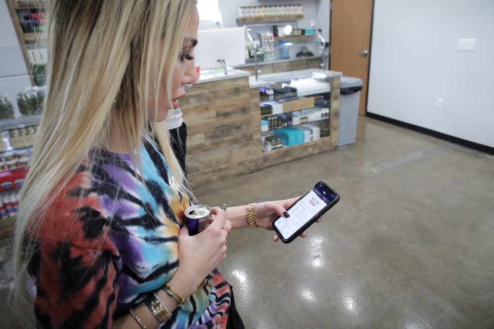 A dispensary manager monitors cannabis retail store performance from a mobile app