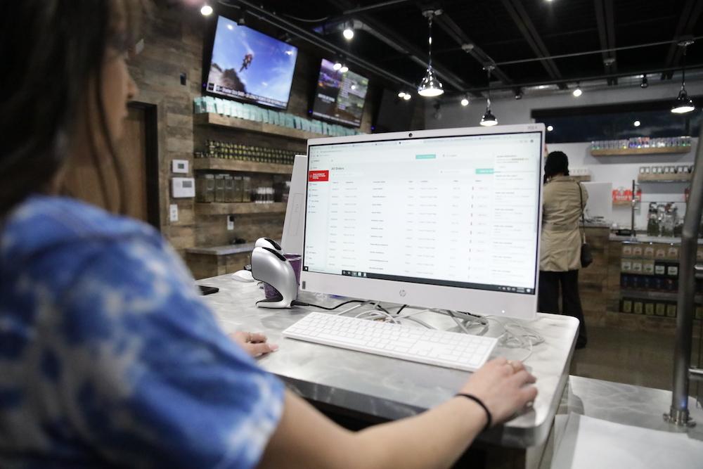 Budtender using Flowhub dispsensary point of sale on desktop computer hardware
